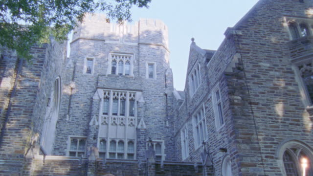 up angle brick building at duke university. pans down on students walking on campus. - ivy league university stock videos and b-roll footage
