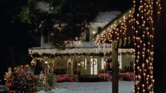 pan right to left to two story middle class house with christmas lights or decorations. snow. - anno 2002 video stock e b–roll