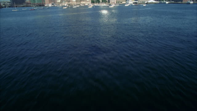aerial over water in ocean, harbor or bay to boston city skyline. skyscrapers and high rise office or apartment buildings in downtown. boats. - new england östra usa bildbanksvideor och videomaterial från bakom kulisserna