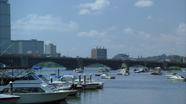 PAN RIGHT TO LEFT ACROSS BOSTON HARBOR AND LONGFELLOW BRIDGE. BOSTON CITY SKYLINE IN BG. HIGH RISES AND SKYSCRAPERS. BOATS AND YACHTS IN MARINA AND HARBOR. CHARLES RIVER. COMMUTER TRAIN MOVES ACROSS BRIDGE FROM LEFT TO RIGHT.
