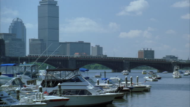 pan right to left across boston harbor and longfellow bridge. boston city skyline in bg. high rises and skyscrapers. boats and yachts in marina and harbor. charles river. commuter train moves across bridge from right to left. - マリーナ点の映像素材/bロール