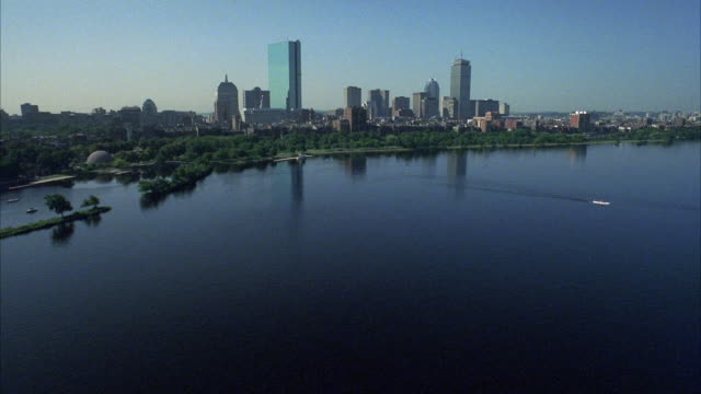 vídeos de stock e filmes b-roll de aerial over charles river, longfellow bridge. back bay, upper class residential area. multi-story brick townhouses or apartment buildings. skyscrapers or high rise office buildings and john hancock tower in bg. city skyline. - back bay boston