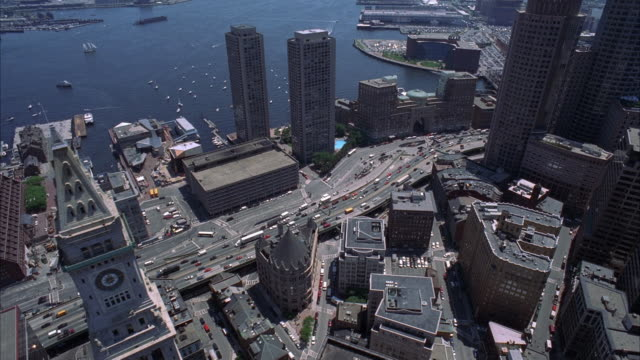 aerial over skyscrapers and high rise office or apartment buildings in downtown boston. boats in bay or harbor. custom house clock tower. - custom house tower stock videos & royalty-free footage
