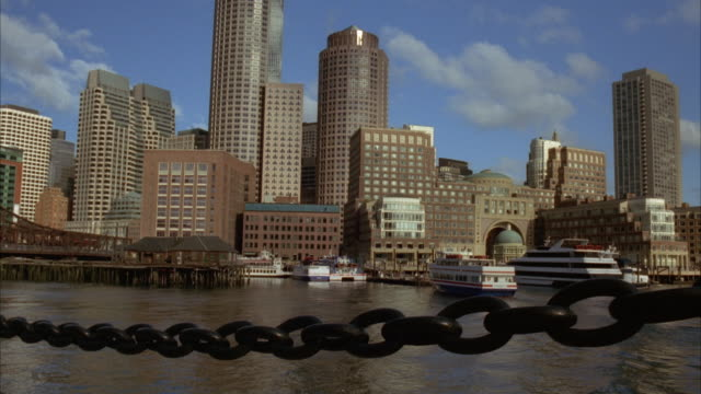 wide angle of boston harbor as ferry moves towards docks. charles river. high rises, skyscrapers, and office buildings. boston city skylines. black chain in fg. - river charles stock videos & royalty-free footage