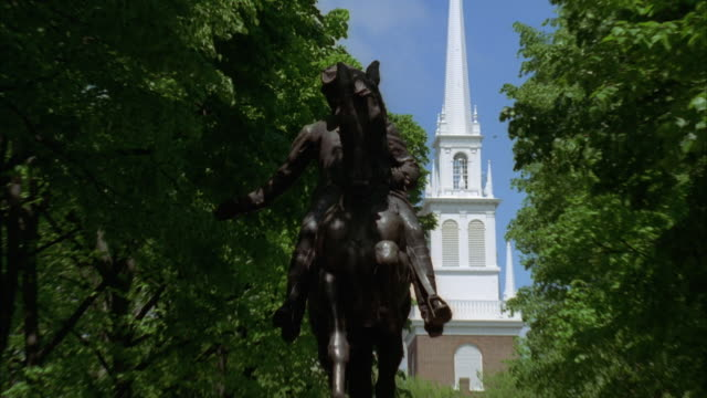 pull back form close angle of statue of paul revere on horse. old north church visible in  bg.  paul revere mall in north end of boston. trees line street. tourists. - old north church stock videos & royalty-free footage