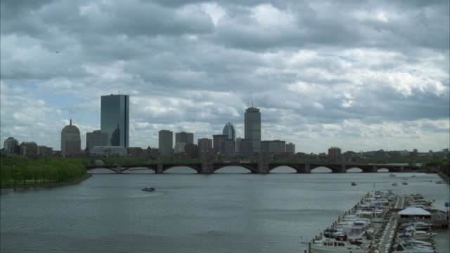 WIDE ANGLE OF CHARLES RIVER WITH LONGFELLOW BRIDGE IN BG. DOWNTOWN BOSTON SKYLINE. CLOUDY SKY. FERRY BOAT. MARINA IN FG.