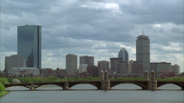 WIDE ANGLE OF CHARLES RIVER WITH LONGFELLOW BRIDGE IN BG. DOWNTOWN BOSTON SKYLINE. CLOUDY SKY.