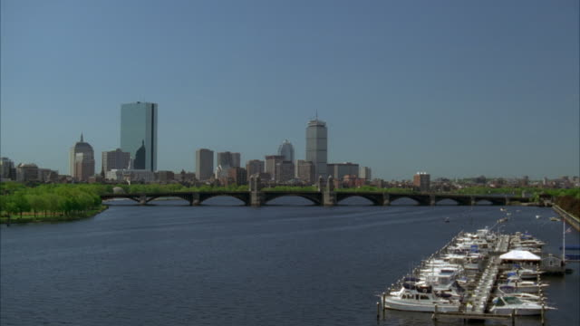 wide angle of charles river and boston harbor with longfellow bridge and boston skyline. john hancock tower in bg. boats anchored in marina. boston harbor. - back bay stock-videos und b-roll-filmmaterial