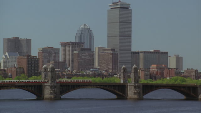 pan up from water of charles to river to longfellow bridge and boston skyline. john hancock tower in bg. boats anchored in marina. boston harbor. train moves across bridge. - back bay stock-videos und b-roll-filmmaterial