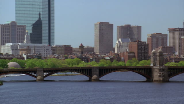 PAN RIGHT TO LEFT ACROSS BOSTON CITY SKYLINE WITH LONGFELLOW BRIDGE AND CHARLES RIVER IN FG. BOSTON HARBOR. HIGH RISES, SKYSCRAPERS, AND OFFICE BUILDINGS. RED FERRY IN FG.  PARK IN FG.
