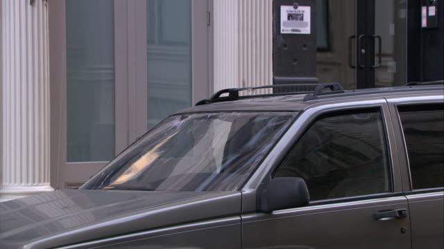 medium angle of brick falling on top windshield of jeep grand cherokee suv or car. broken window. - windschutzscheibe stock-videos und b-roll-filmmaterial
