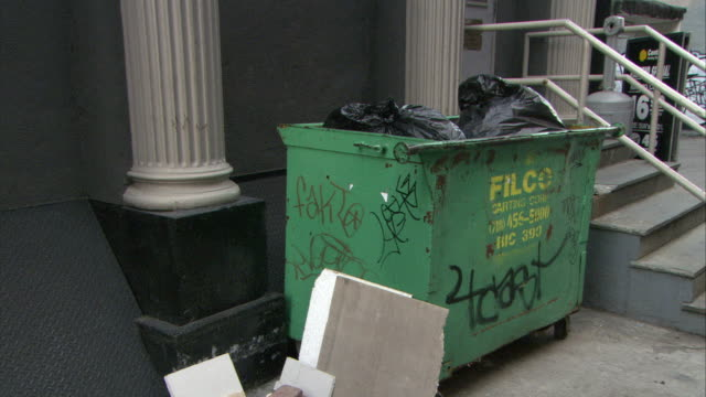 MEDIUM ANGLE OF DUMPSTER WITH TRASH OR GARBAGE.