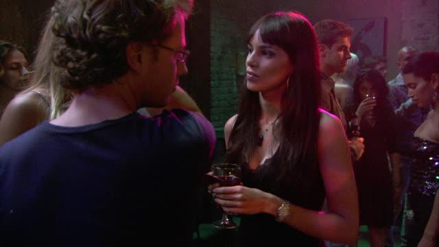 medium angle of people mingling, talking in bar. woman flirting with man. - flirten stock-videos und b-roll-filmmaterial