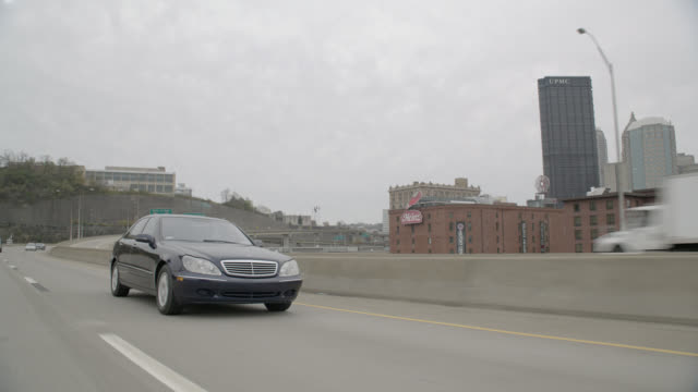 tracking shot of mercedes benz driving on city street or freeway. high rise office buildings visible in bg. bridges visible. - dolly shot stock videos & royalty-free footage