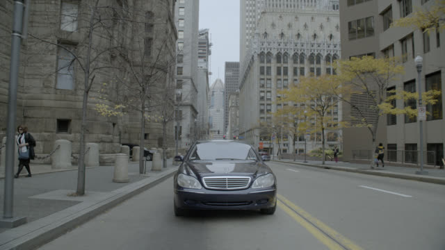 tracking shot of mercedes benz car driving on city streets. high rise office buildings visible. - dolly shot stock videos & royalty-free footage