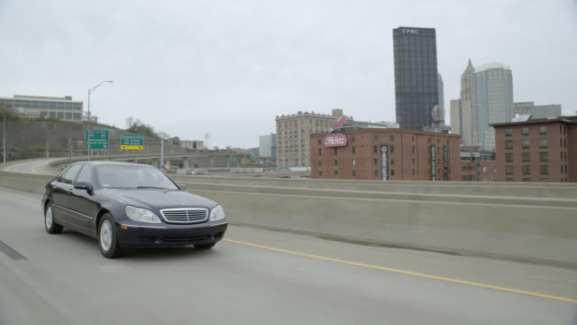 tracking shot of mercedes benz car driving on freeway or highway outside city. city skyline visible in bg with high rise office buildings. - mercedes benz stock videos and b-roll footage