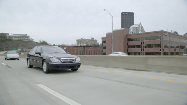 tracking shot of mercedes benz car driving on freeway or highway outside city. city skyline visible in bg with high rise office buildings. - mercedes benz stock videos & royalty-free footage