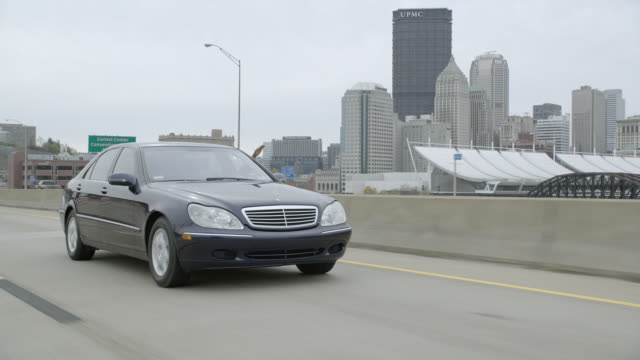 tracking shot of mercedes benz car driving on freeway or highway outside city. city skyline visible in bg with high rise office buildings. - トラッキングショット点の映像素材/bロール