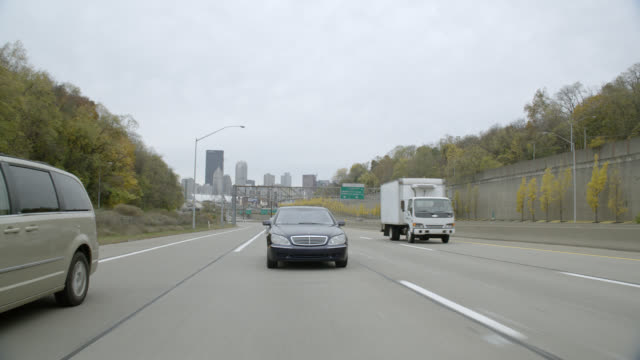 tracking shot of mercedes benz car driving on freeway or highway outside city. could be interstate. pittsburgh city skyline visible in bg. - mercedes benz stock videos & royalty-free footage