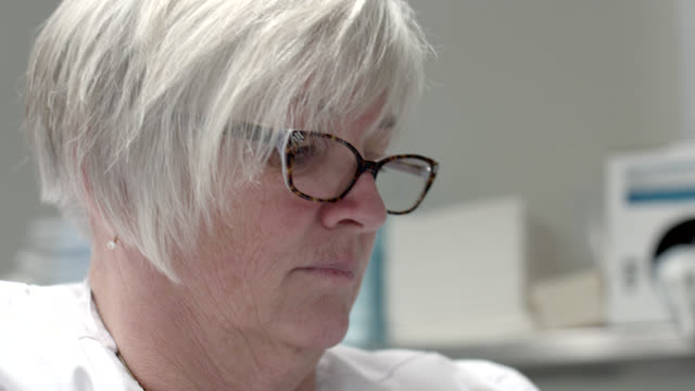 close angle of woman in glasses and white shirt. out of focus medical equipment visible in bg. could be nurse or doctor in hospital or laboratory. - white shirt stock videos & royalty-free footage