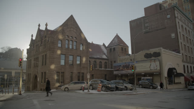 wide angle of  old allegheny county mortuary or morgue building in downtown pittsburgh. small parking lot visible. pedestrians visible at stoplight or crosswalk. - pompe funebri video stock e b–roll