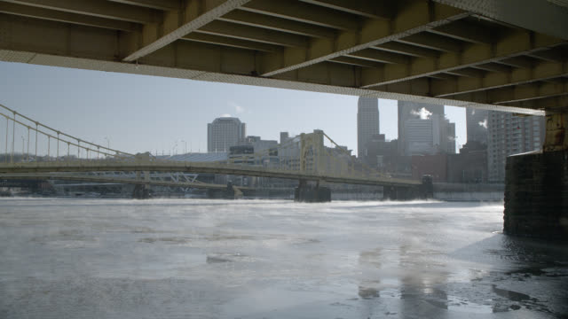 MEDIUM ANGLE OF ALLEGHENY RIVER AND PITTSBURGH SKYLINE FROM UNDER RACHEL CARSON BRIDGE. ANDY WARHOL AND ROBERTO CLEMENTE BRIDGES VISIBLE IN BG. PNC PARK VISIBLE IN BG.