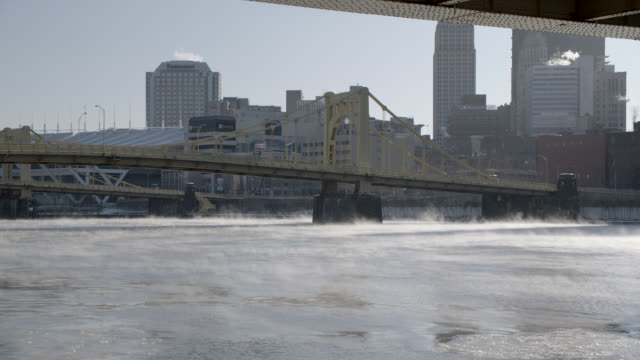 MEDIUM ANGLE OF ALLEGHENY RIVER AND PITTSBURGH SKYLINE FROM UNDER RACHEL CARSON BRIDGE. ANDY WARHOL AND ROBERTO CLEMENTE BRIDGES VISIBLE IN BG. PNC PARK VISIBLE IN BG. FROST OR MIST RISING FROM WATER.