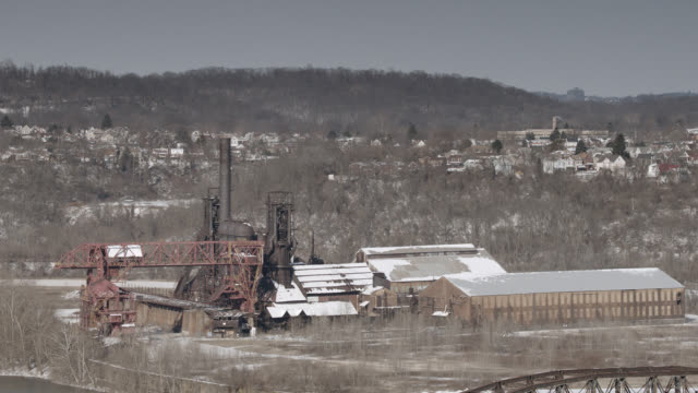 MEDIUM ANGLE OF CARRIE FURNACES HISTORIC LANDMARK WITH MONONGAHELA RIVER. RAILROAD BRIDGE PARTIALLY VISIBLE. SNOW.