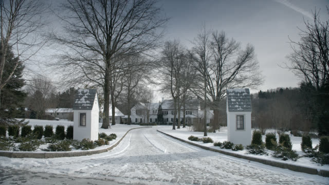 wide angle of upper class mansion, house, or estate, guard booths at driveway. snow covered driveway. - ostamerika stock-videos und b-roll-filmmaterial