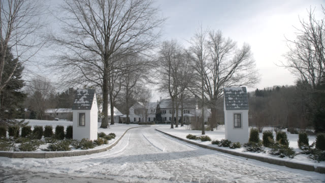 wide angle of upper class mansion, house, or estate, guard booths at driveway. snow covered driveway. - eastern usa stock videos & royalty-free footage