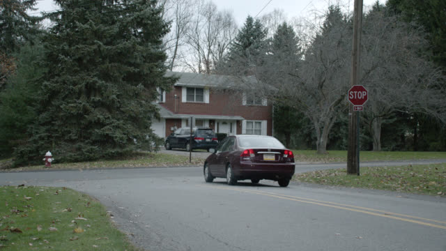 stockvideo's en b-roll-footage met wide angle of cars driving on residential street in rural area. could be suburbs. brick two-story house visible in fg. cars turn right at stop sign. - pennsylvania