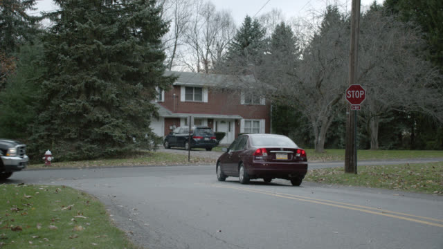 wide angle of cars driving on residential street in rural area. could be suburbs. brick two-story house visible in fg. cars turn right at stop sign. - zweistöckiges wohnhaus stock-videos und b-roll-filmmaterial