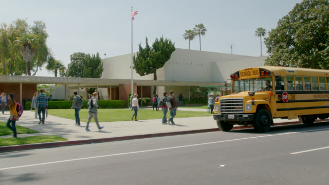 stockvideo's en b-roll-footage met process plate driving 3/4 right back of school bus arriving at front of middle school. students. - school building