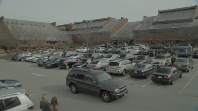 vidéos et rushes de medium angle of cars in parking lot of brick buildings. could be community center or community college. - centre culturel