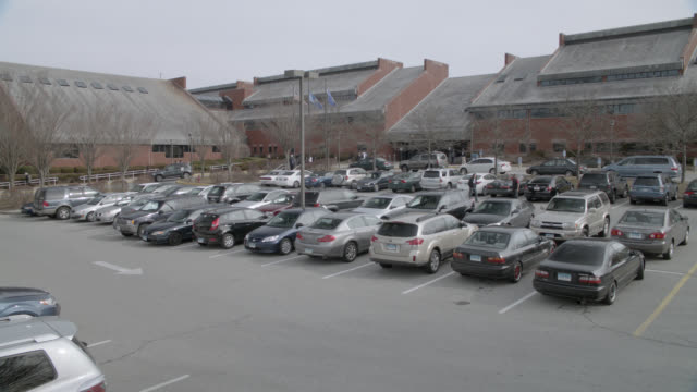 medium angle of cars in parking lot of brick buildings. could be community center or community college. - community center stock videos and b-roll footage