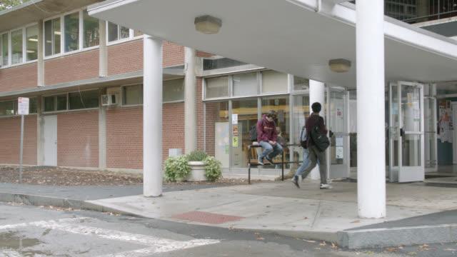 vídeos y material grabado en eventos de stock de pan left to right of students walking by entrance to school or library. - biblioteca