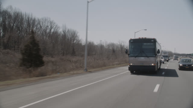 wide angle driving pov 3/4 right back of charter bus going to new york city. - bus stock videos & royalty-free footage