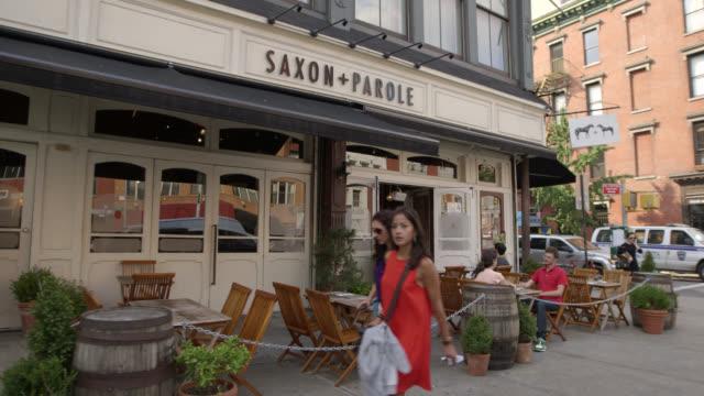 medium angle of restaurant on city street corner in greenwich village. people or pedestrians on sidewalk. - greenwich village stock videos & royalty-free footage