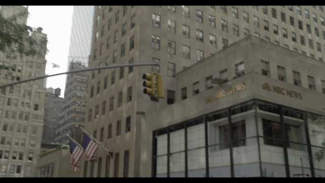 pan up of nbc news offices, rockefeller center. skyscrapers or high rise buildings in bg. people or pedestrians on sidewalk. - nbcuniversal stock videos & royalty-free footage