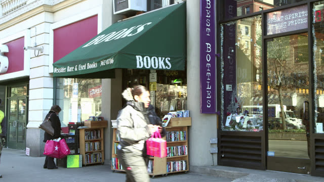 medium angle of bookstore. people or pedestrians on sidewalk. shopping. - bookstore stock videos & royalty-free footage