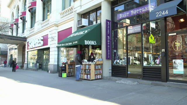 wide angle of bookstore. people or pedestrians on sidewalk. shopping. - book shop stock videos & royalty-free footage