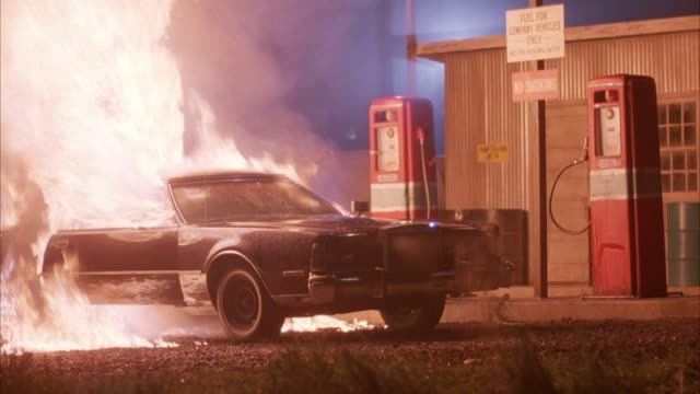 """medium angle of black chrysler new yorker parked at gas station with sign above that says """"fuel for company vehicles only."""" with two pumps. car explodes into flames that spreads to gas station. neg cut. chrysler car. explosions. fires. - 1980 stock videos and b-roll footage"""