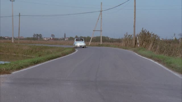 medium angle of paved road surrounded by dry grass field and canal. see small light blue european car driving towards pov. see dump truck and compact red convertible enter frame moving away from pov. see man and woman in blue car stop in front of camera a - blue convertible stock videos & royalty-free footage