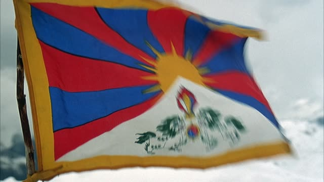 MEDIUM ANGLE OF FLAG OF TIBET BLOWING IN WIND ON SNOWY MOUNTAIN TOP.