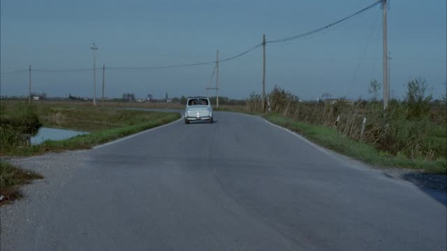 medium angle stunt. see paved road surrounded by dry grass field and canal. see small light blue european car driving towards pov. see dump truck and compact red convertible enter frame moving away from pov. see red convertible drive in front of blue car - blue convertible stock videos & royalty-free footage