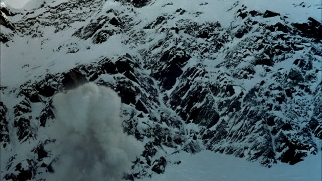 medium angle of snow strewn boulders and rocks. could be snowy mountain side or slope. see small explosion send up puff of smoke or snow at bottom left. see avalanche of snow fall from top. see clouds of smoke or snow obstruct pov.  see partial body of mo - natural disaster stock videos & royalty-free footage