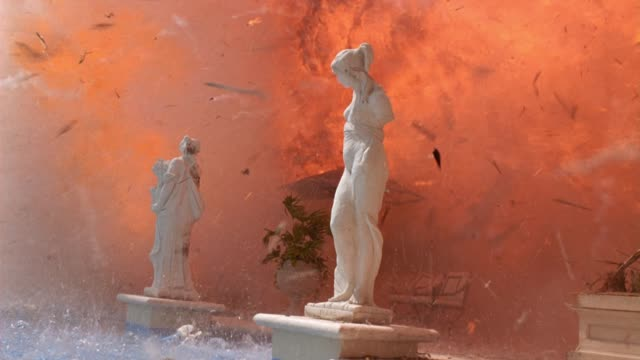 vidéos et rushes de wide angle of explosion at mansion or two story upper class house. fire, flames, smoke. debris flying. classical greek or roman statues near swimming pool and patio. palm trees, tropical. playback. 5.1 surround sound. 2225-020. - palmier