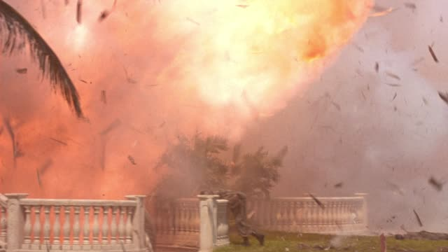 pan left to right of explosion at mansion or two story upper class house. fire, flames, smoke. debris flying. classical greek or roman statues near swimming pool and patio. palm trees, tropical. dead bodies of guards or soldiers. playback. 5.1 surround so - stately home stock videos & royalty-free footage