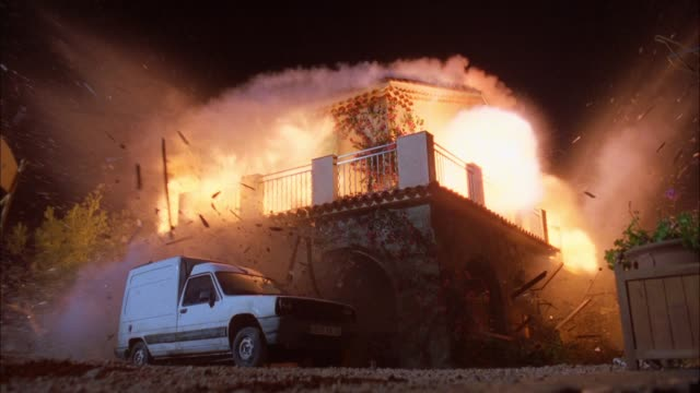 vídeos de stock e filmes b-roll de wide angle of two story middle class house, could be spanish or mediterranean style. white truck parked in front. explosion, fire, flames, smoke. broken windows, glass, debris. playback, 5.1 stereo surround sound. 6095-038. - explodir