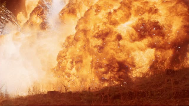 vídeos de stock e filmes b-roll de wide angle of explosions going through trees in woods or forest. sparks. fires, flames, smoke. could be during attack. playback, 5.1 stereo surround sound. 6167-070. - explodir